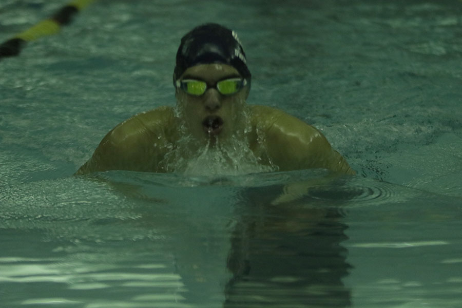 Taking a breath, junior Cole McClure swims the 100 meter breaststroke.