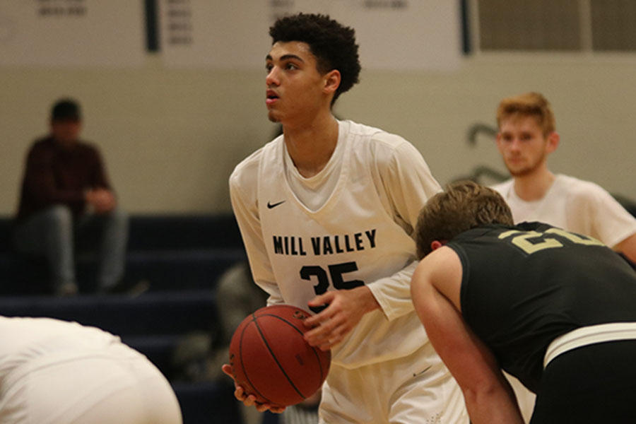 Staying focused, sophomore Adrian Dimond gets ready to shoot a free throw, making it and scores a point. The team lost to Blue Valley Jan. 14, the final score being 65-52.