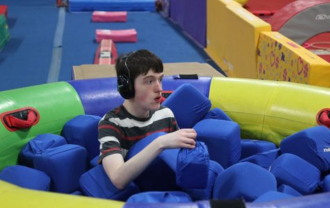 Sitting in a foam pit sophomore John Carl, plays with the foam cubes at Pinnacle Gymnastics on Thursday, Jan. 23.