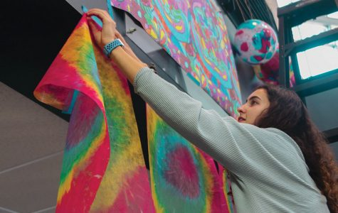 Hanging tie-dye banners in the main entrance, junior Nicole Crist attends StuCo's spirit week decorating on Sunday, Jan. 5.
