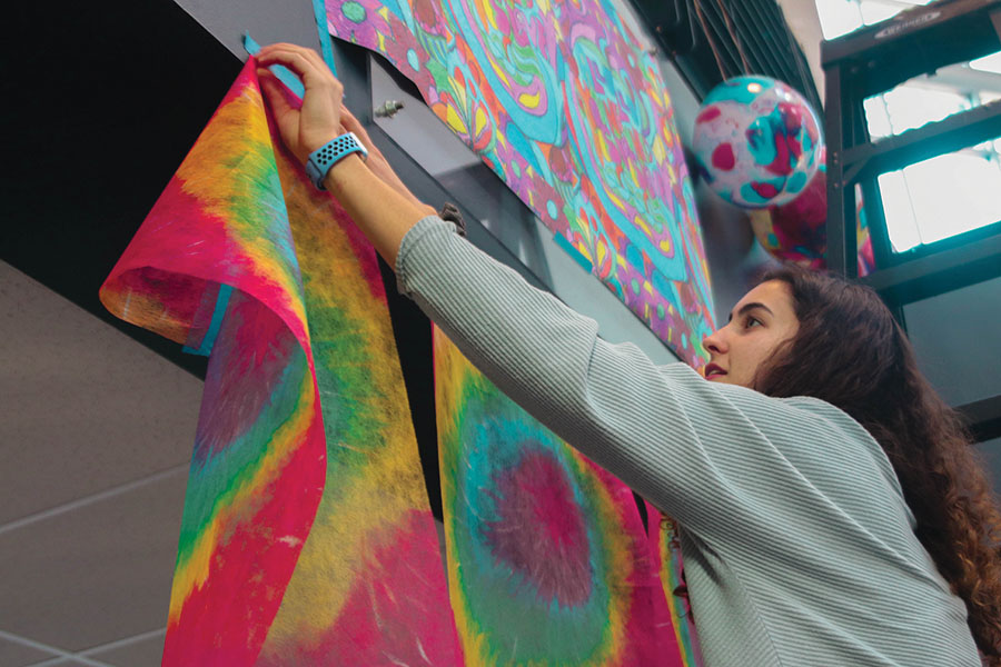 Hanging+tie-dye+banners+in+the+main+entrance%2C+junior+Nicole+Crist+attends+StuCo%27s+spirit+week+decorating+on+Sunday%2C+Jan.+5.