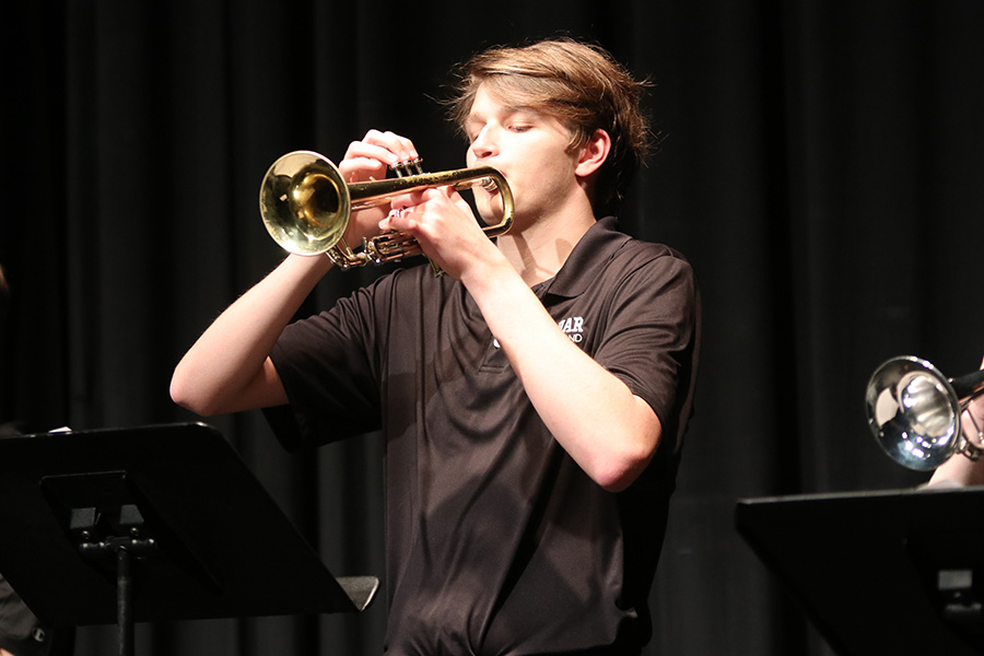 Standing with his trumpet, senior Nathan Greenfield plays his trumpet.