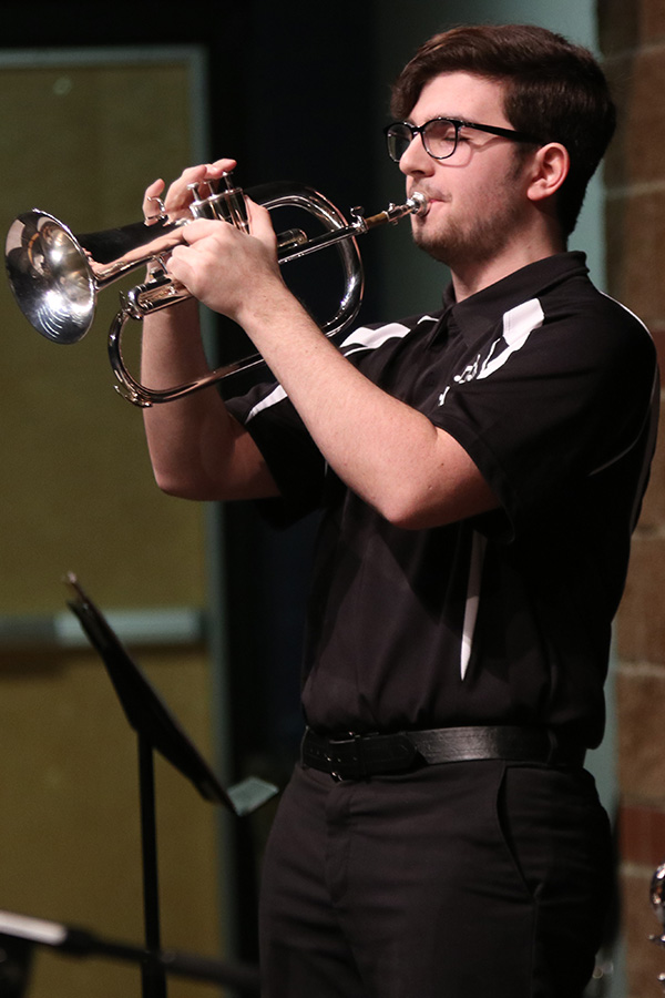 Standing during his solo, junior Jason Kingsbury plays the flugelhorn.