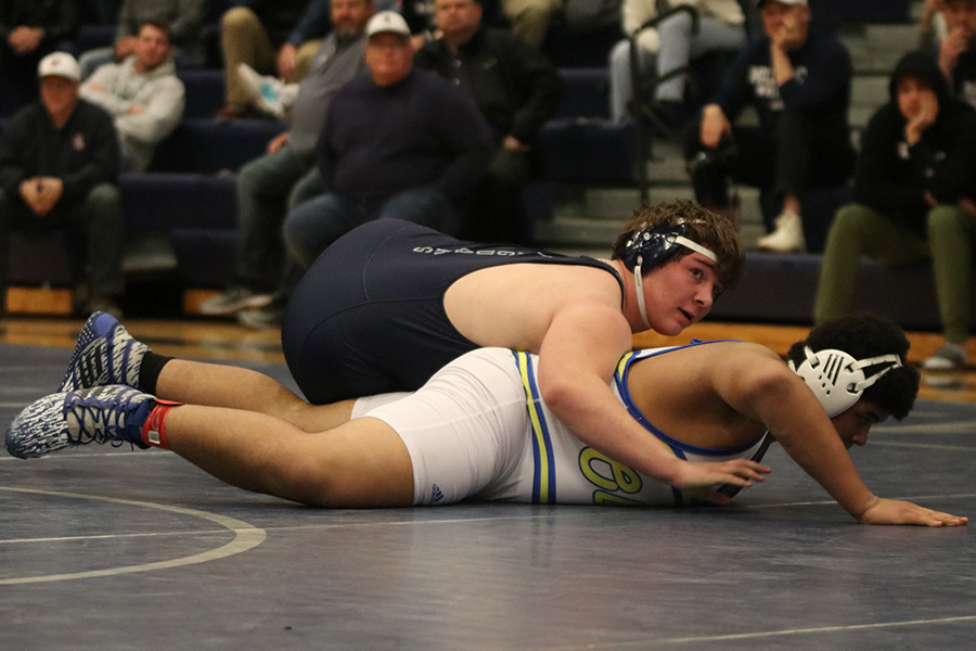 Leaning over his opponent, junior Ethan Kremer looks to his coaches for advice on his next move.