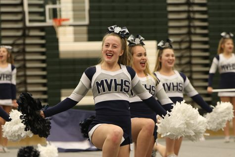 Kneeling to the ground, junior Emma Moore puts on a smile while shaking her pom-poms.