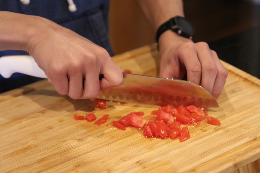 After browning the meat, senior Nico Gatapia dices a tomato to add to the dish later.