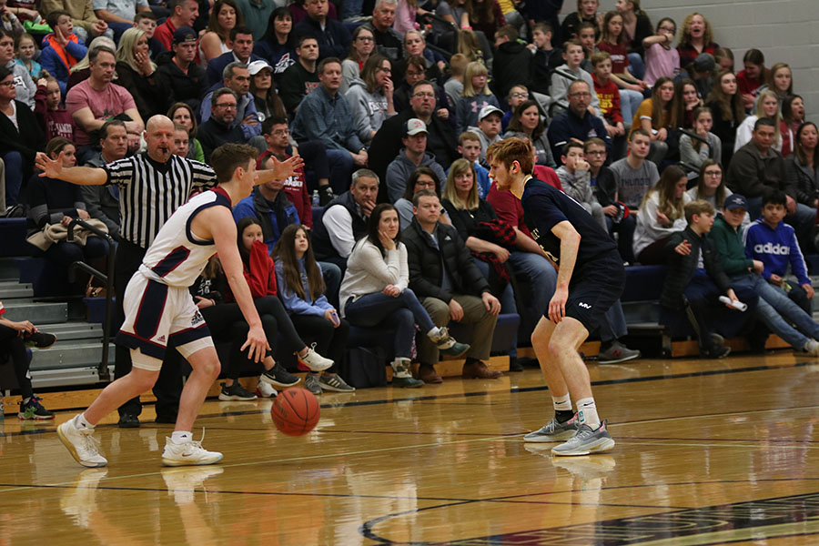 Guarding an offensive player, senior Braeden Wiltse watches the ball closely. On Friday, Feb. 7, boys basketball fell to St. James in an end score of 52-42.