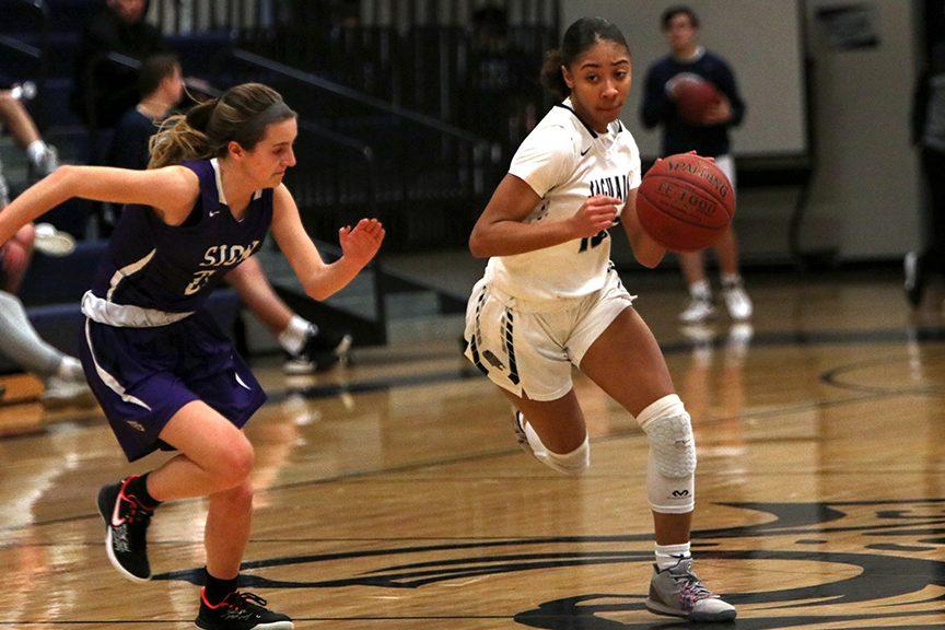 Running toward the basket, junior Vania Barnett avoids a defender. The team defeated Notre Dame de Sion 44-40 Tuesday, Feb. 26 on senior night.