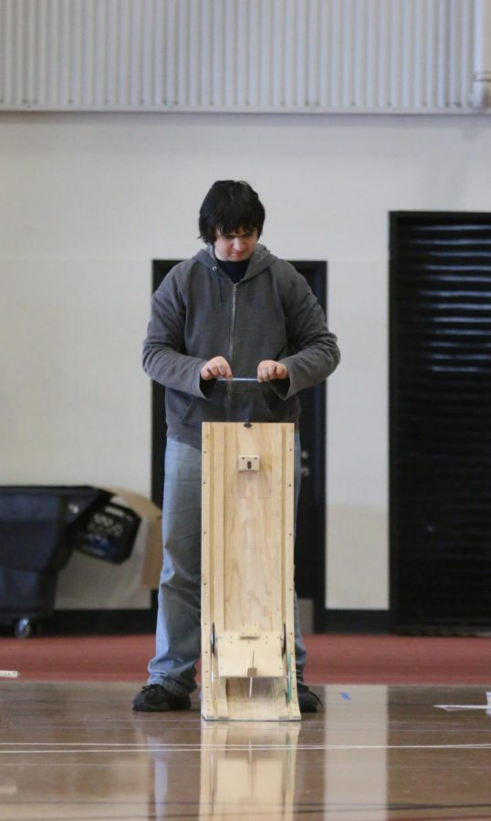 After setting up the vehicle ramp for the event Gravity Vehicle, junior Andrew Gawith uses a pencil to release the vehicle from its initial vertical position at the top. Gravity Vehicle is an event where a team of up to two attempts to build a ramp and vehicle to reach a designated location; the closer the vehicle can make it to the marked point, the better. Gawith and his partner, sophomore Jordan Manning, placed fifth overall.