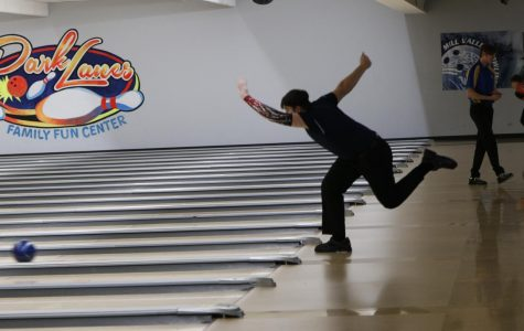 Throwing the ball, junior Devin Khulman extends his arm toward the pins. The Mill Valley Bowling team competed at regionals at Park Lanes Thursday, Feb. 27.