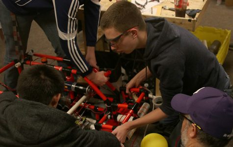 A group of students on the robotics team make a change to their robot's design at practice Thursday, Feb 6.