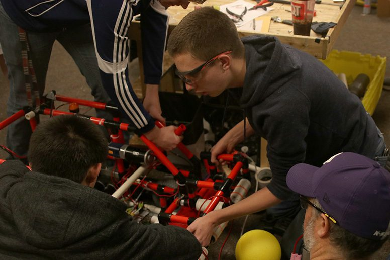 A+group+of+students+on+the+robotics+team+make+a+change+to+their+robot%E2%80%99s+design+at+practice+Thursday%2C+Feb+6.%0A