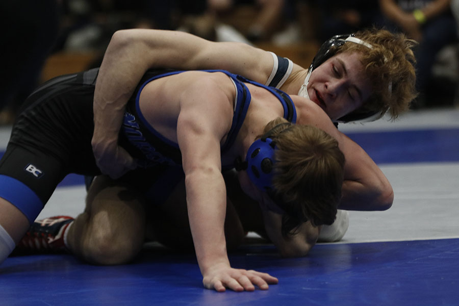 With a tight hold on his opponent, senior Cole Moberly looks to take control of the match.