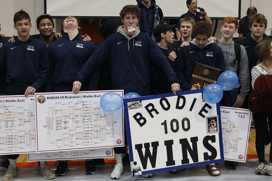 Standing with his teammates, junior Brodie Scott celebrates his 100th victory.
