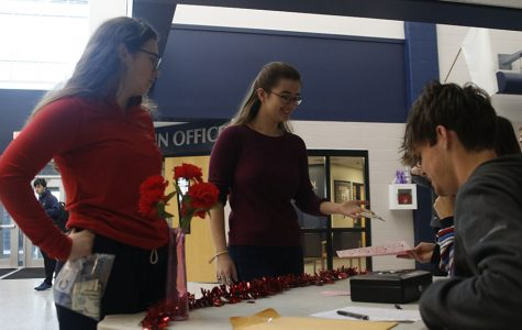 Handing the English NHS members money, senior Joan Downey and sophomore Allision Rader buy carnations Thursday Feb. 7.