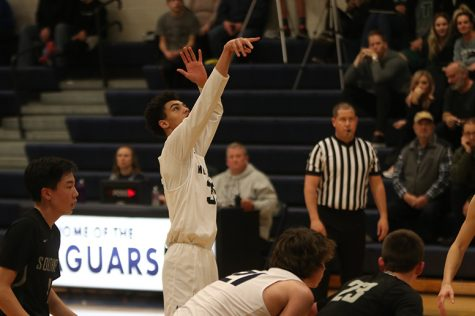 Arms in the air, sophomore Adrian Dimond shoots a free throw. On Tuesday, Feb. 26, the boys basketball team defeated Blue Valley Southwest 54-39.