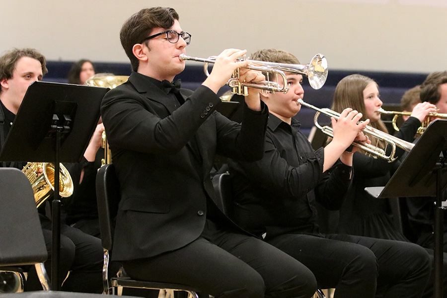 Playing for the audience, senior Jason Kingsbury solos in the middle of the song standing out of the crowd.