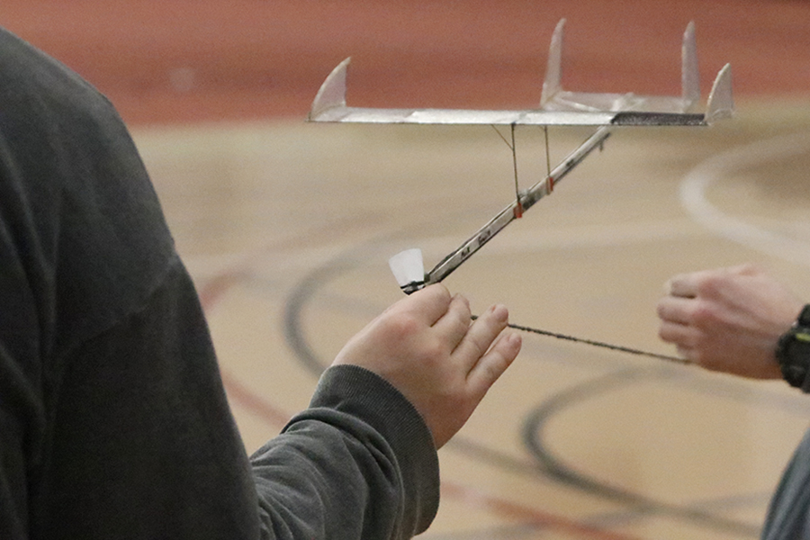 Working together, sophomore Patrick Mack and junior Andrew Gawith wind up the rubber band that spins the propeller.