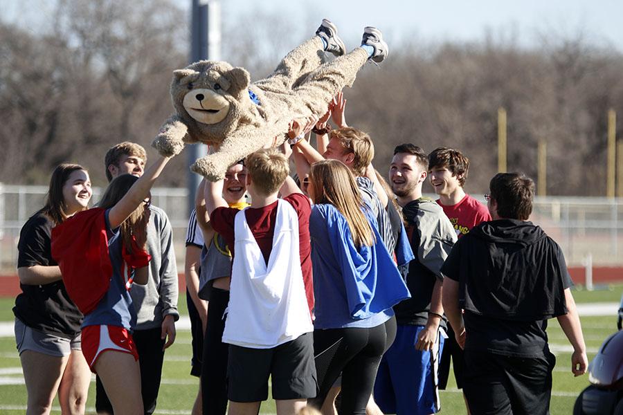Wearing a bear costume, freshman Eli Olsen is held up by his teammates.