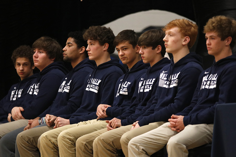 Members of the varsity wrestling team look out into the crowd as speakers congratulate them on their state title.
