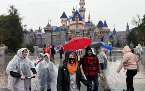 A guest wears a face mask in front of the Sleeping Beauty Castle while visiting Disneyland amid rain showers in Anaheim, Calif., on March 12, 2020. Disneyland will temporary close the Disneyland Resort in Anaheim in response to the expanding threat posed by the Coronavirus Pandemic. The closure takes effect Saturday and lasts through the end of March. Disneyland and Disney California Adventure will close Saturday morning through the end of the month in response to Gov. Gavin Newsom and state health officials' recommendation that gatherings of 250 or more people be canceled across the state, company officials said.