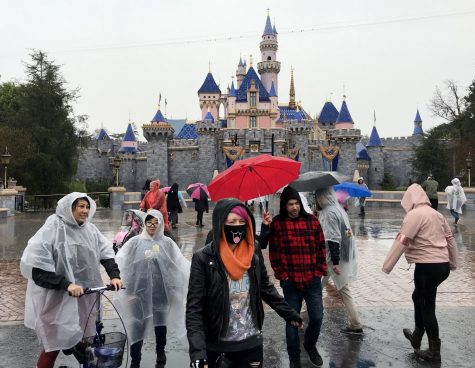 A guest wears a face mask in front of the Sleeping Beauty Castle while visiting Disneyland amid rain showers in Anaheim, Calif., on March 12, 2020. Disneyland will temporary close the Disneyland Resort in Anaheim in response to the expanding threat posed by the Coronavirus Pandemic. The closure takes effect Saturday and lasts through the end of March. Disneyland and Disney California Adventure will close Saturday morning through the end of the month in response to Gov. Gavin Newsom and state health officials