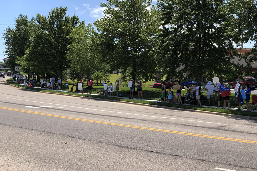 Holding signs and shouting chants, families gather on the sidewalk along Hilltop Drive to share a message to drivers.