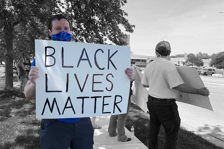 In+light+of+the+Black+Lives+Matter+movement%2C+Shawnee+community+members+gathered+at+Monticello+Library+Sunday%2C+June+14+to+protest+against+police+brutality.+Nearly+100+civilians+participated+in+the+protest%2C+holding+up+signs+and+shouting+chants+to+cars+passing+by.