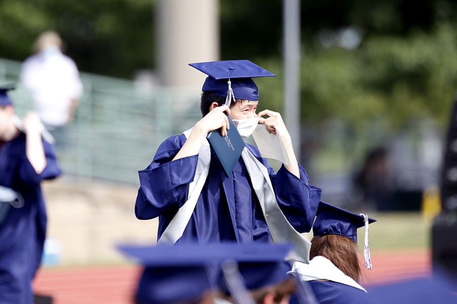 After getting his picture taken, senior Kevin Lee puts his mask back on his face as he makes his way back to his seat.