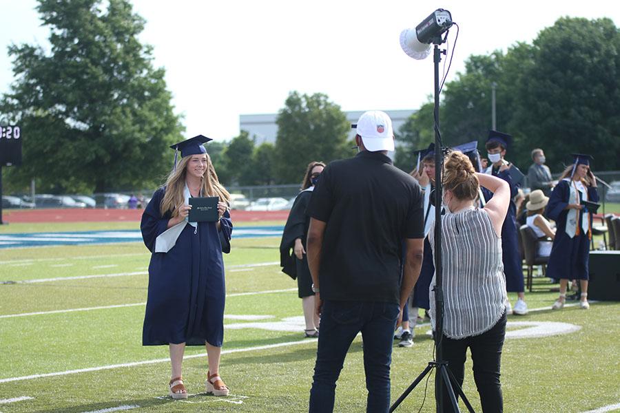 Posing for photos, senior Gabi Fitterer smiles and holds up her diploma.