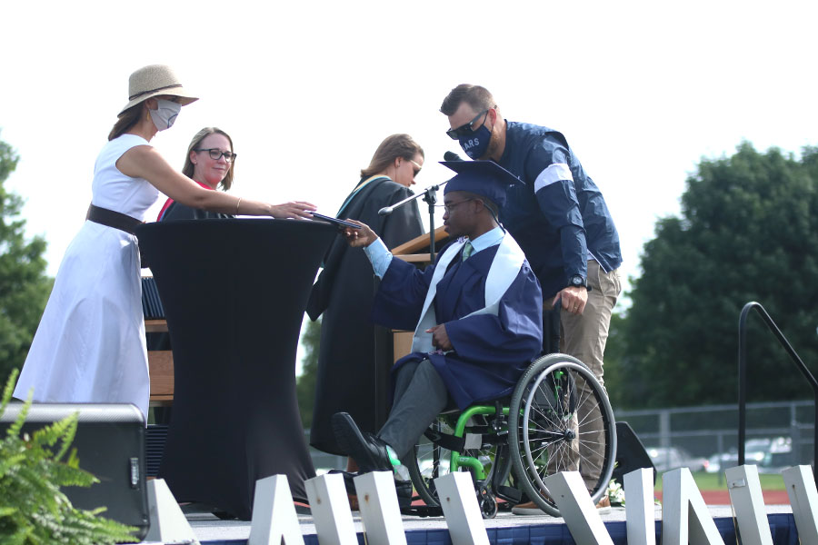 Helping senior Nathaniel Lee get his diploma, special education teacher Zach McFall wheels Lee across the stage.