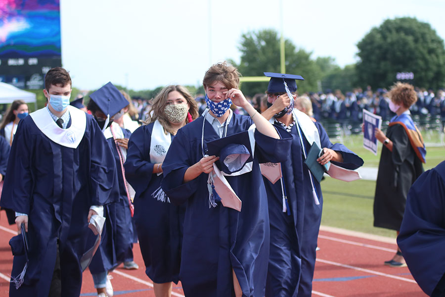 Wiping away tears, senior Jake Keller walks away from the field where the ceremony was held to meet with friends and family.