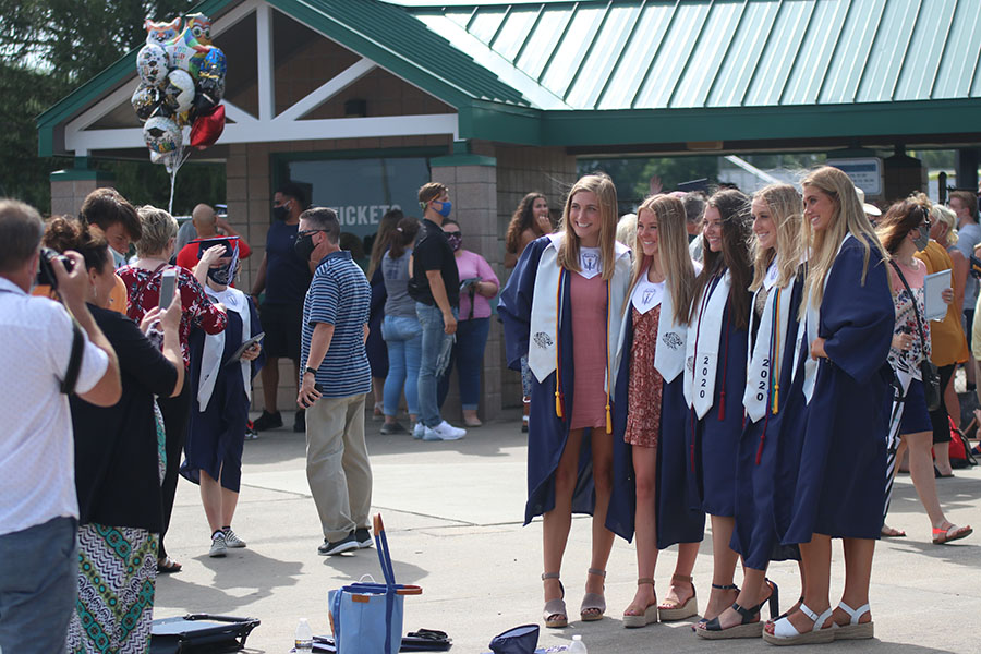 A group of senior girls pose for a photo in their cap and gown following the commencement of the ceremony.