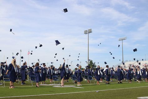 In a celebratory manner, the senior class of 2020 throws their graduation caps in the air on Saturday, July 25.