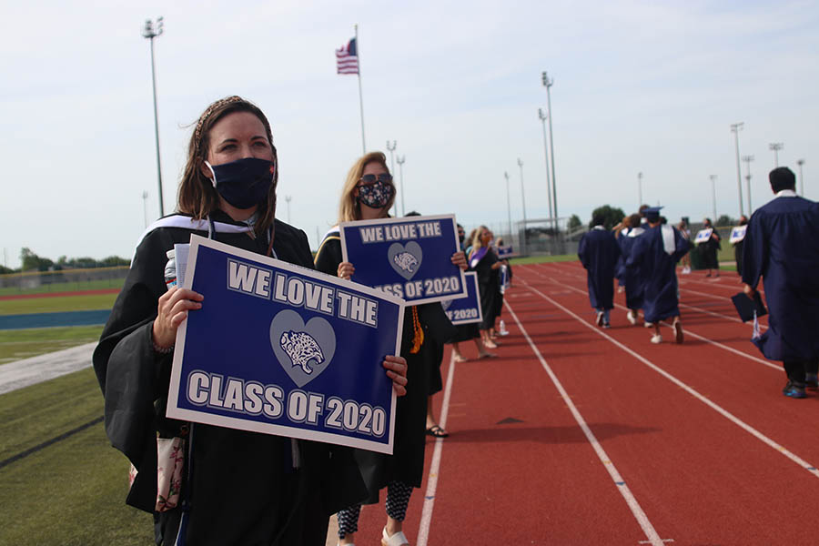 While students make their way out of the field where the ceremony itself was held, teachers such as art teacher Erica Crist, held up congratulatory signs.