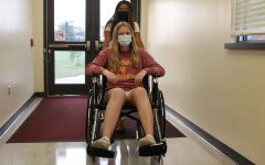 Pushing junior Kelly Doyle in the wheelchair, junior Jada Eggleston practices wheelchair use.