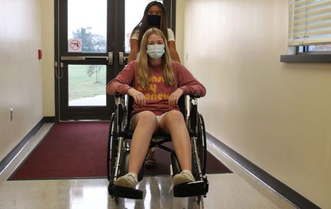 Pushing junior Kelly Doyle in the wheelchair, junior Jada Eggleston practices wheelchair use.