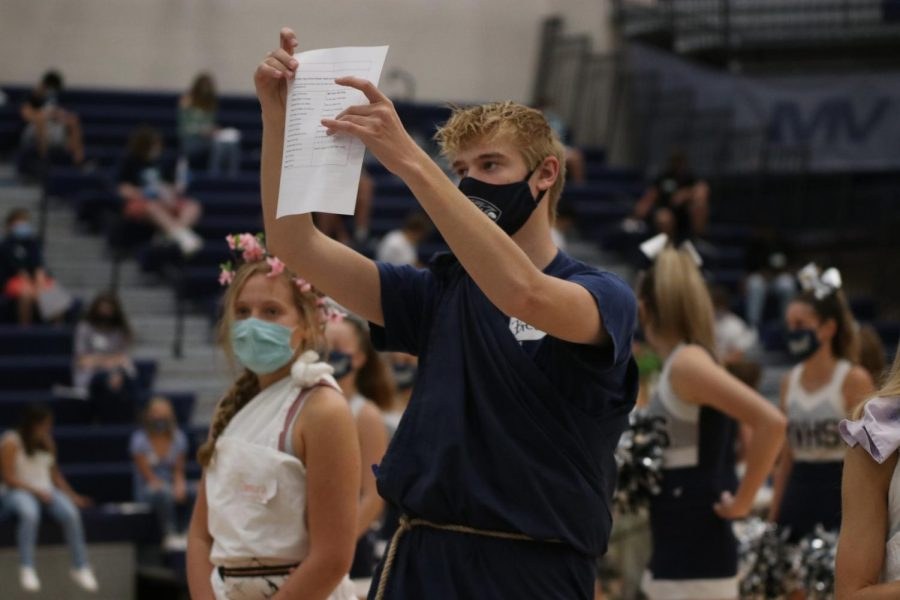 Preparing the freshmen to learn the fight song, junior Bret Weber holds up the paper that has the lyrics for them to read.