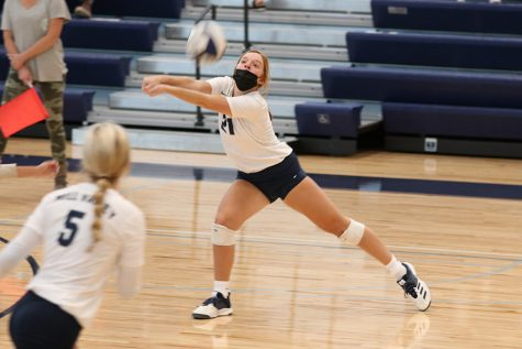 Eyes on the ball, junior Brylee Peterson bumps the ball over the net.The girls volleyball team won a triangular against Olathe South and Olathe West, beating South in two sets and West in three sets. They played Thursday, Sept. 17 in the new home gym.