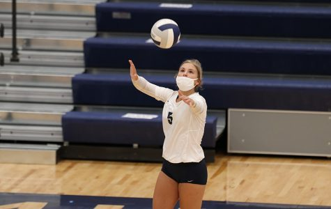Tossing the ball in front of her, senior Anna Judd begins to serve to the other team. The Mill Valley volleyball team won the first three sets against Leavenworth Tuesday, Sept. 1 in the new gym, leaving the final score 3-0.