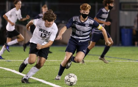 Next to an opponent, sophomore Owen Peachee races to the ball. The boys soccer team tied 3-3 against Shawnee Mission West while playing at home Thursday, Sept. 24.