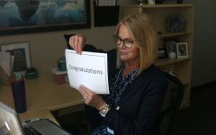 "To honor students named National Merit Scholarship semifinalists, principal Dr. Gail Holder holds a sign reading ""Congratulations"" on a Zoom call Wednesday, Sept. 9."