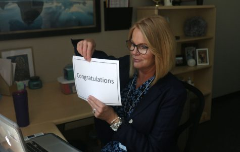 """To honor students named National Merit Scholarship semifinalists, principal Dr. Gail Holder holds a sign reading """"Congratulations"""" on a Zoom call Wednesday, Sept. 9."""