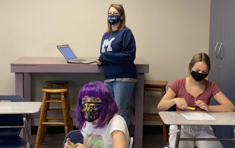 English teacher Ashley Agre clicks through a presentation for her freshman English class from the back of the classroom.