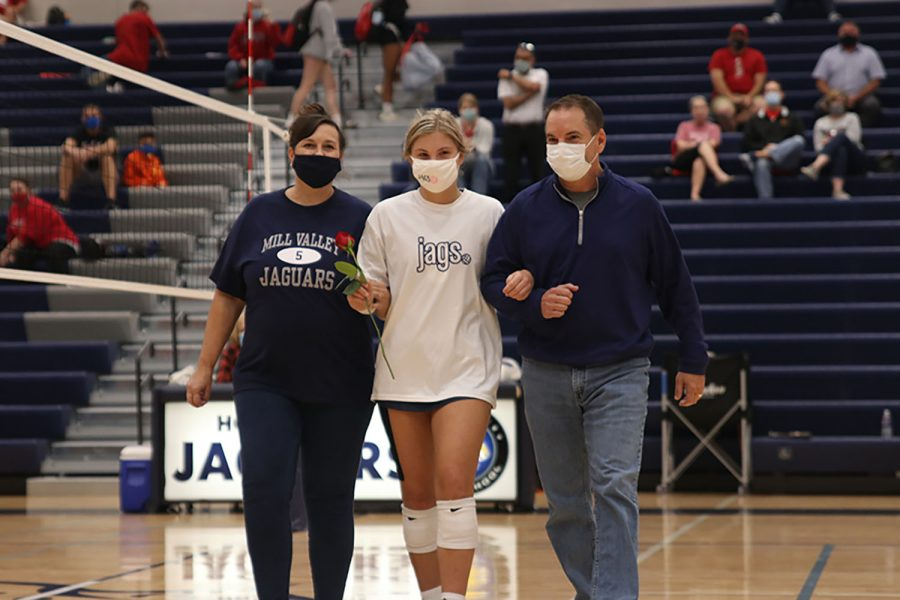 Walking with her parents, senior Anna Judd is recognized for senior night. The girls volleyball team won a triangular against Lawrence High School and Lawrence Free State on Tuesday, Sept. 29, beating Lawrence in 2 sets, and Lawrence Free State in 3 sets.