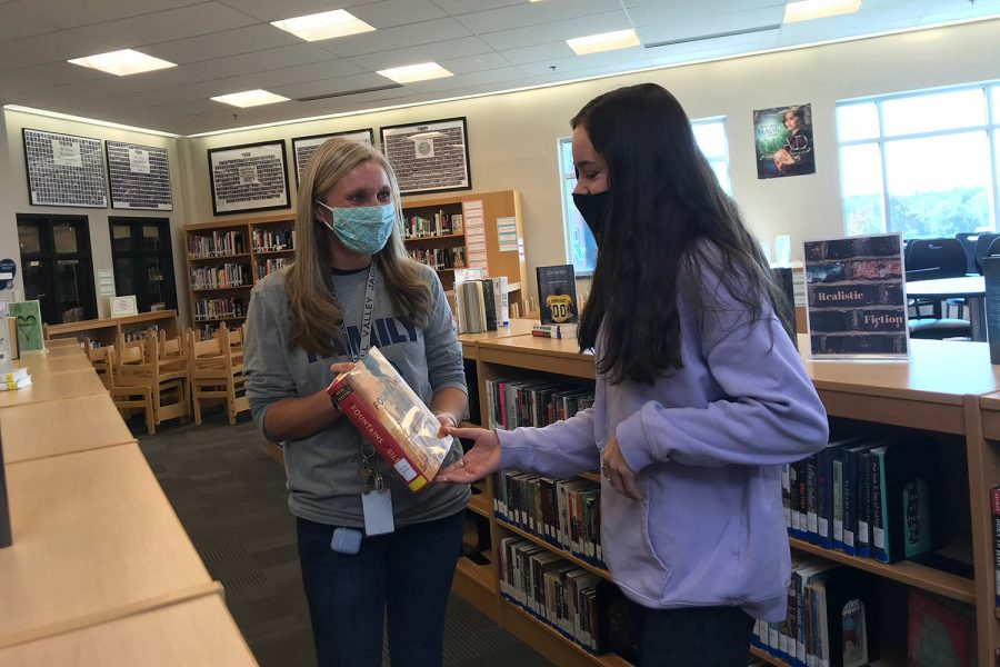 Ashley Bennett shares book recommendations and Book Club information with a member of her club.