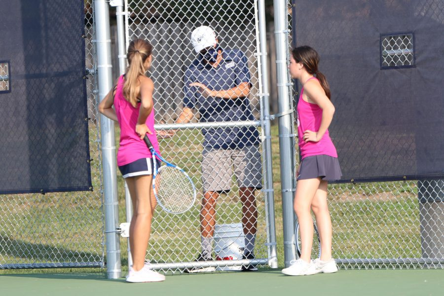In between a match, junior Eden Schanker and senior Avery Rutkowski talk with assistant coach Andrew Bock about how they can play better.