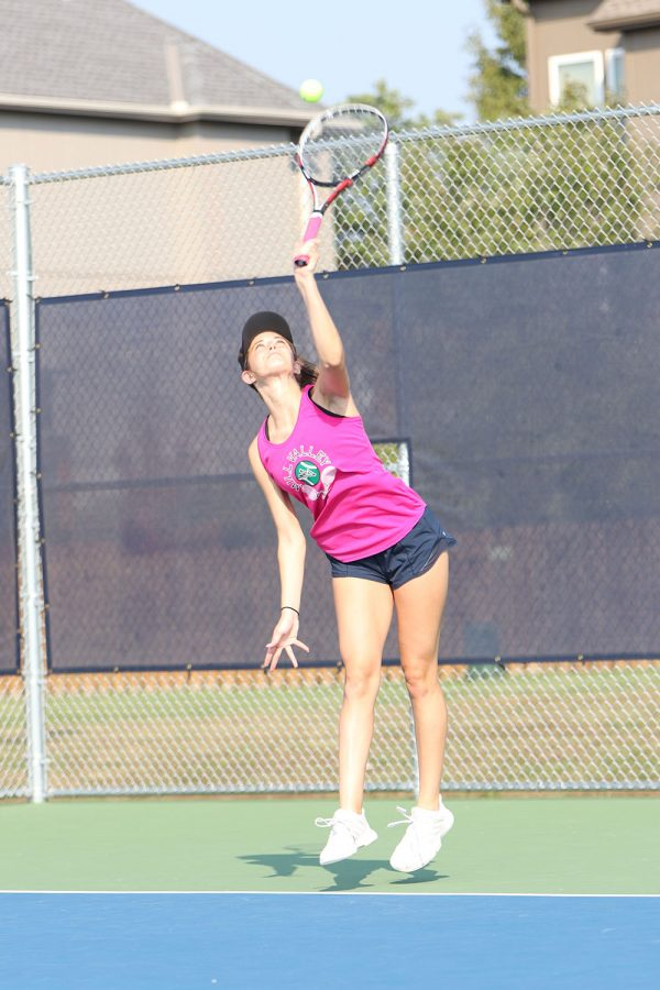 Springing into the air, junior Olivia Lecuru reaches to hit the ball.