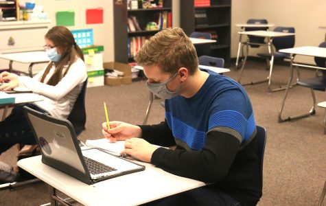 While wearing a mask and practicing social distancing in the classroom, Junior Ben Baumgart works on his in-class french assignment on Thursday, Oct 1.