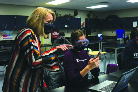 Stepping into science teacher Jill Lloyd's chemistry class, principal Dr. Gail Holder discusses the results of an experiment with a student Friday, Oct. 9.